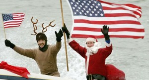 ARLINGTON, VA - DECEMBER 24:  Dressed as Santa Claus, Kerry Nistel (R) holds an American flag after water-skiing along the Potomac River near the Washington Monument December 24, 2003 in Arlington, Virginia. This is the 18th year Nistel has dressed as Santa and water-skied on Christmas Eve.  (Photo by Mark Wilson/Getty Images)